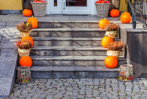 Pumpkins and bushels of apples adorning the stone front steps of a house.