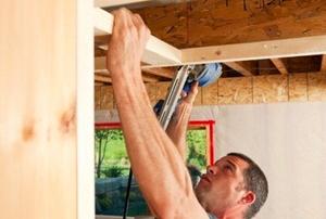 A man installing basement ceiling frames.