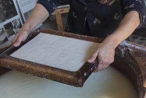 A wood tray of paper pulp held over a basin of water.