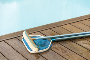 pool brush laying on decking beside the pool
