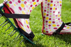 polka dot boots over aerating spike shoes piercing a lawn