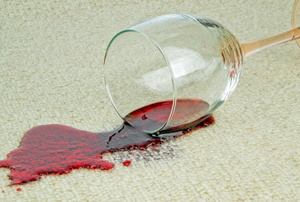 A wine glass knocked over on a carpet with spilled red wine.