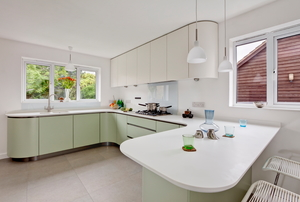 Kitchen with white laminate countertops and green cabinets