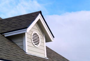 A home exterior showing an attic vent against a blue sky.