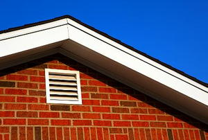 A white gable vent on a brick house.