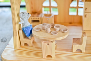 a dollhouse with a stuffed mouse at a tiny table