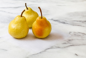 A trio of pears sitting on a marble countertop.