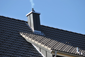 smoke puffing out of chimney on grey roof