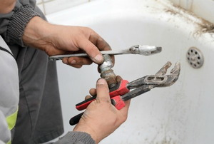 A plumber holding a wrench trying to fix a leaky drain.