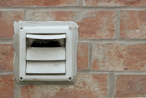 dryer vent mounted to a brick wall