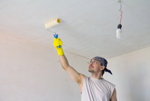 A young man in a bandana painting a ceiling white.