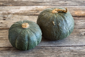 Two winter squash sitting on a wood surface.