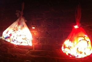Two shopping bag lights against a brick wall.