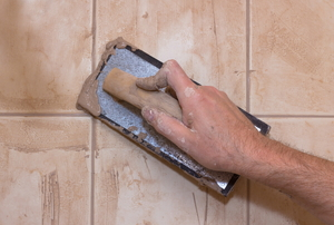 Spreading grout between tiles by hand, leaving some behind.