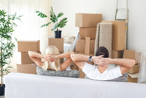 A couple relaxing on a couch on moving day.