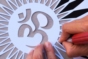 hands cutting elaborate stencil
