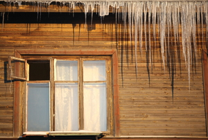 An old house with icicles and an open window.