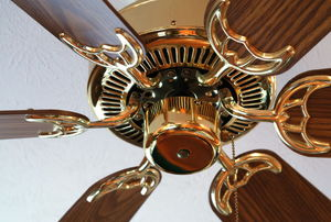 a brown and brass ceiling fan on a white ceiling