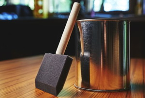 a shiny can with a foam brush on a stained wood surface