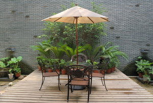 A floating deck with a table and chairs set on it surrounded by plants.