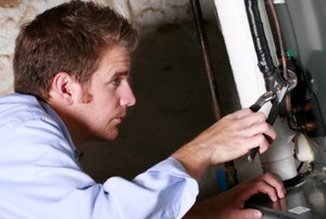 man working on a gas furnace