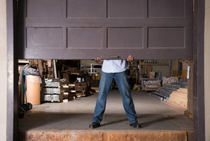 man lifting a brown garage door