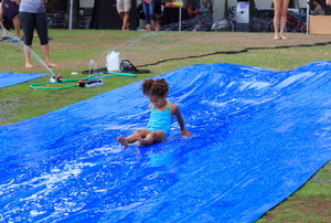 A young girl in a swim suit sliding down a slip 'n slide.