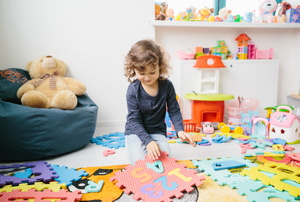 A girl plays on a puzzle mat.