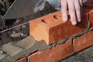 person laying bricks and mortar