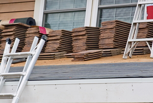 shingles stacked on a roof for installation with ladders nearby