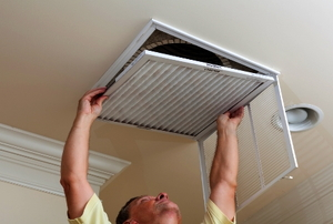 A man reaching up to open filter holder for HVAC in the ceiling.