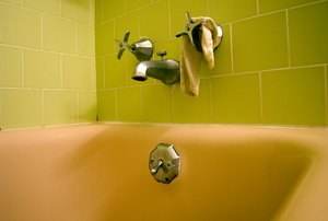 The shower faucet and diverter face plate in a bathroom with green tile.