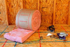 A roll of pink, fiberglass insulation and related tools in front of an unfinished wall.