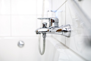A new bathtub faucet with a chrome finish in a white bathroom.