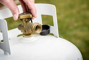 hand turning the valve on a propane tank