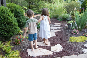 Two kids walk down a garden path.