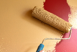 roller painting light tan color over dark red wall