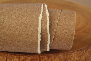 A roll of sandpaper on a wood background.