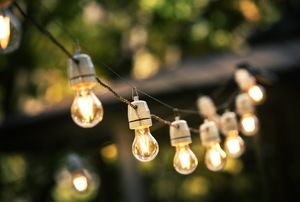 A string of outdoor lights with lit bulbs.