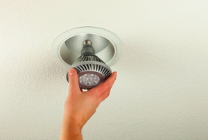Installing an energy efficient LED light bulb into a ceiling can fixture.
