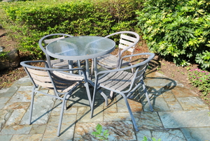 A glass patio table with matching metal-frame chairs.