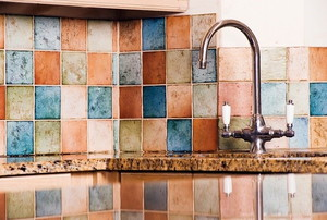 A kitchen backsplash made of colorful ceramic tiles.