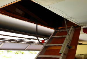 A metal ladder leading up to an above-garage storage area.