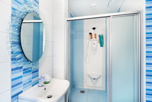 A blue bathroom with a sliding shower door.