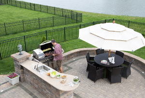 An aerial view of an outdoor kitchen with a table and BBQ.