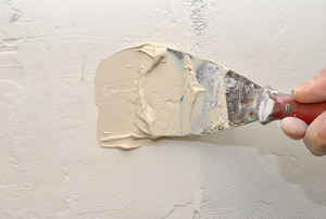 patching drywall with plaster and a putty knife