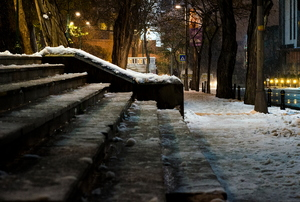A set of snowy stairs outside a building at night.