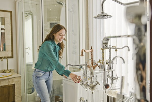 A woman looks at bathroom fixtures.