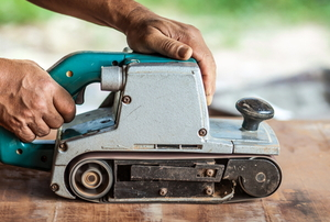 hands using belt sander device