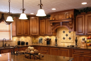 kitchen with drop lights and dark cabinets